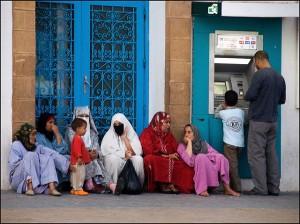 Un groupe de femmes mendiants au pied d'un distributeur de billets à Essaouira (Maroc 2009)/ Photographie Alain Bachellier ( Flickr c.c)